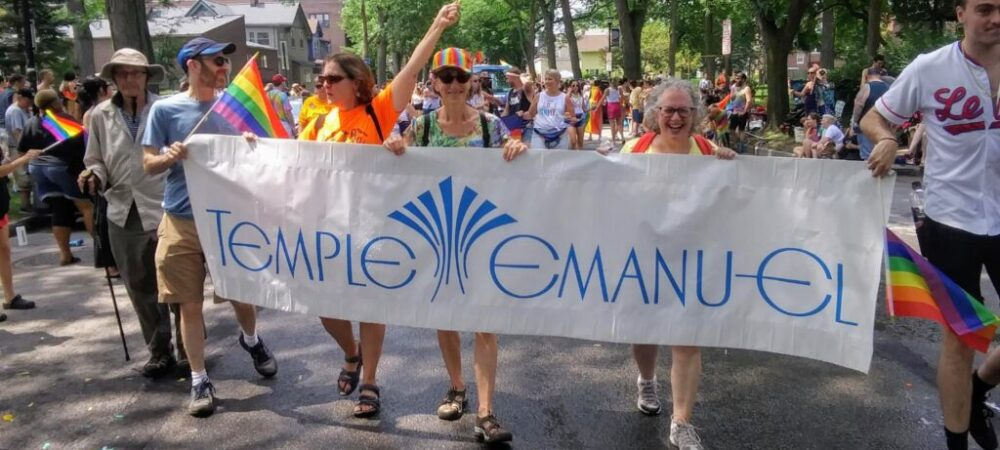 Marching in Pride Parade with large Temple Emanu-El sign