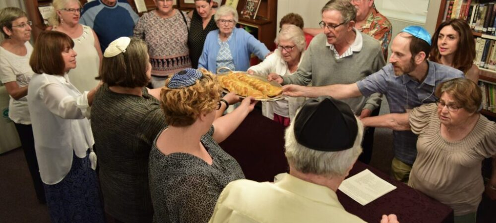 Temple members saying the blessing over the Shabbat challah
